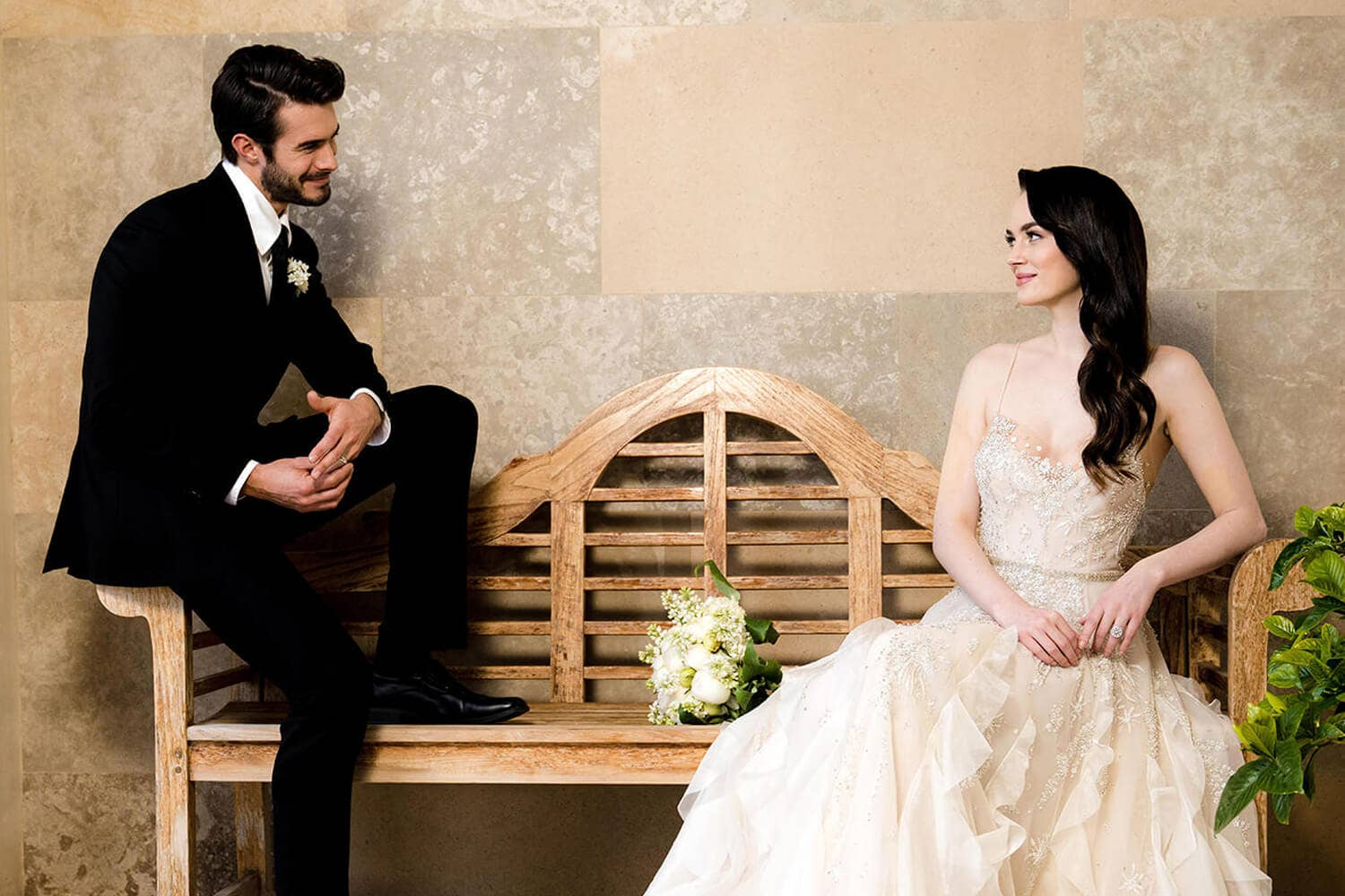 Groom & Bride looking at each other while sitting on a bench